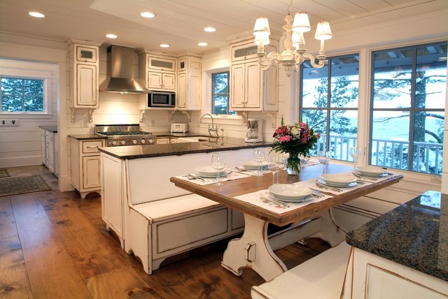 Eat-in kitchen - mid-sized beach style u-shaped dark wood floor and brown floor eat-in kitchen idea in Grand Rapids with a farmhouse sink, recessed-panel cabinets, distressed cabinets, solid surface countertops, white backsplash, wood backsplash, stainless steel appliances and no island