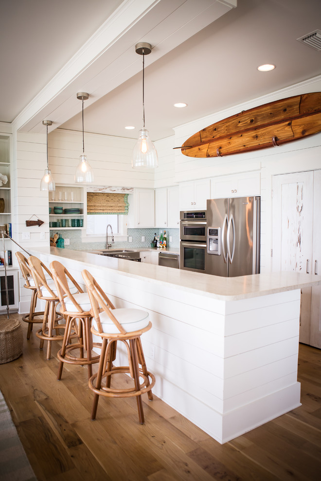 Open concept kitchen - coastal l-shaped open concept kitchen idea in Other with stainless steel appliances and white cabinets