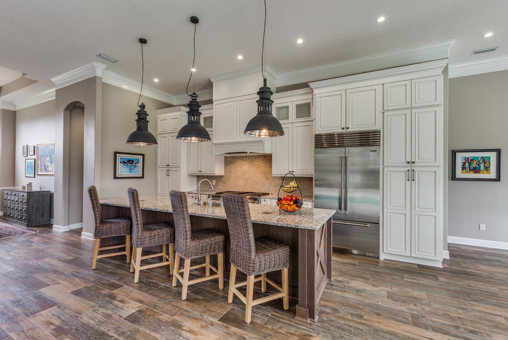 Beach style porcelain tile and brown floor kitchen photo in Jacksonville with raised-panel cabinets, beige cabinets, quartz countertops, marble backsplash, stainless steel appliances, an island, an undermount sink and beige backsplash