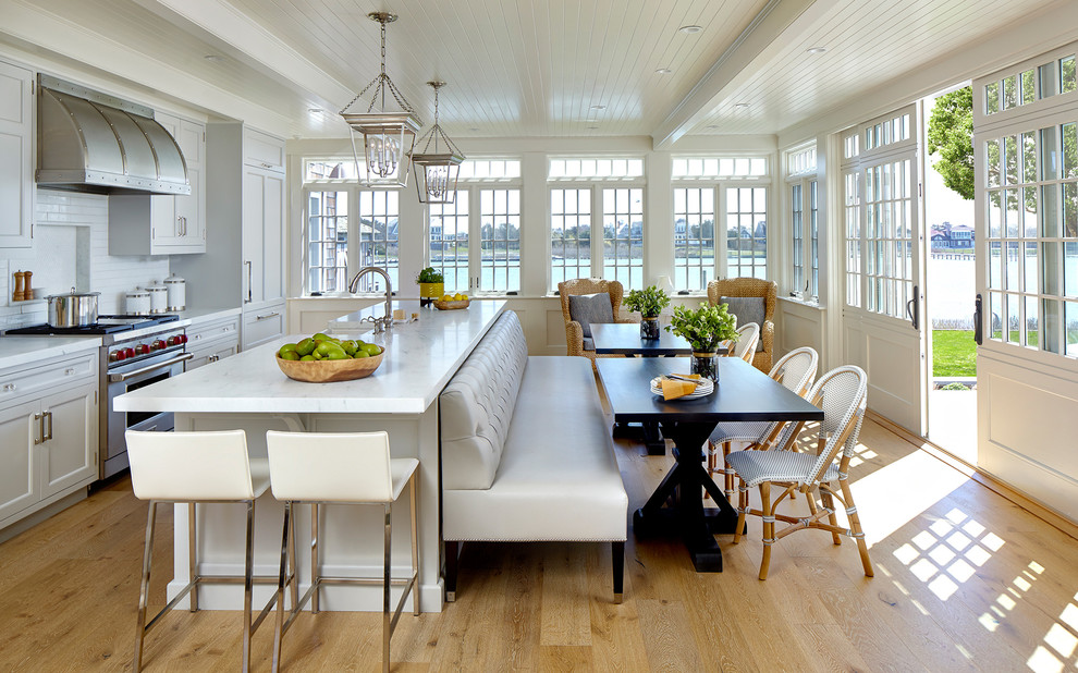 Eat-in kitchen - coastal light wood floor eat-in kitchen idea in New York with recessed-panel cabinets, gray cabinets, white backsplash, subway tile backsplash, stainless steel appliances, an island and white countertops
