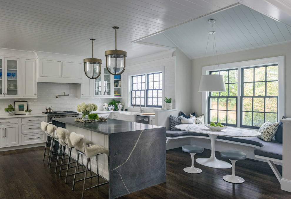 Beach style dark wood floor and brown floor eat-in kitchen photo in Boston with a farmhouse sink, recessed-panel cabinets, white cabinets, white backsplash, stainless steel appliances and an island