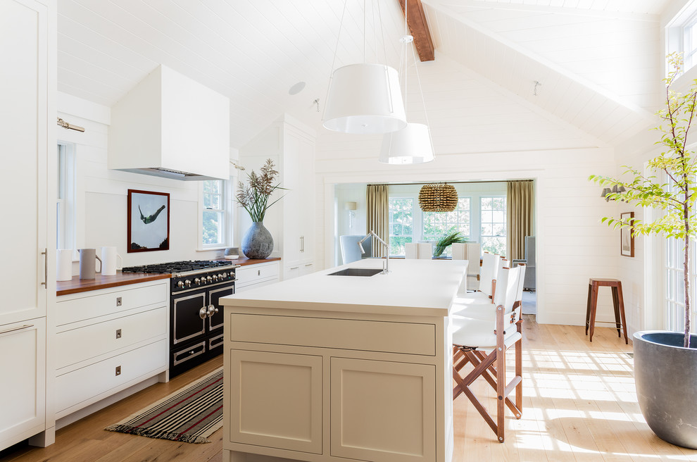 Kitchen - large coastal galley light wood floor kitchen idea in Other with an undermount sink, shaker cabinets, white cabinets, quartzite countertops, white backsplash, black appliances and an island