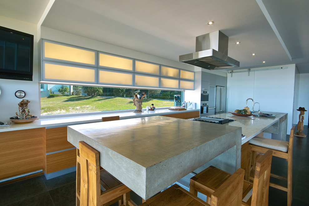 Inspiration for a mid-sized coastal galley eat-in kitchen remodel in Brisbane with an undermount sink, glass-front cabinets, light wood cabinets, concrete countertops, glass sheet backsplash and stainless steel appliances