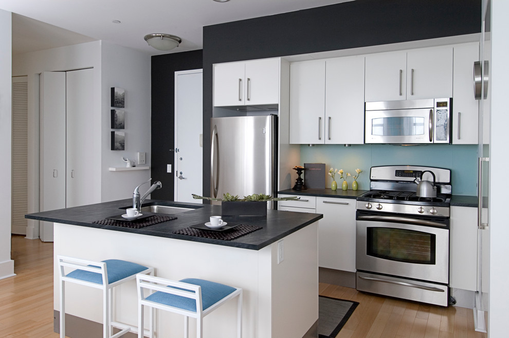 Example of a trendy kitchen design in New York with an undermount sink, flat-panel cabinets and white cabinets