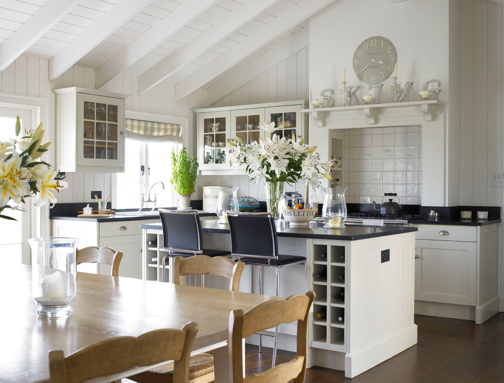 Inspiration for a mid-sized cottage l-shaped dark wood floor eat-in kitchen remodel in Wiltshire with a farmhouse sink, shaker cabinets, white cabinets, granite countertops, an island, white backsplash and ceramic backsplash