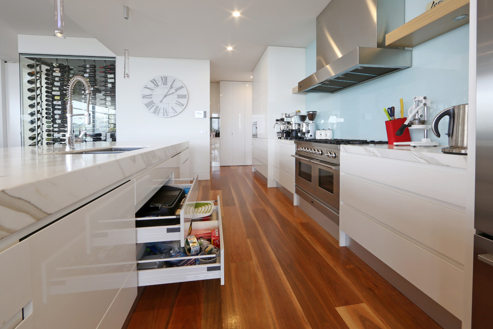 Photo of a contemporary galley kitchen in Melbourne with an undermount sink, flat-panel cabinets, white cabinets, blue splashback, glass sheet splashback and stainless steel appliances.
