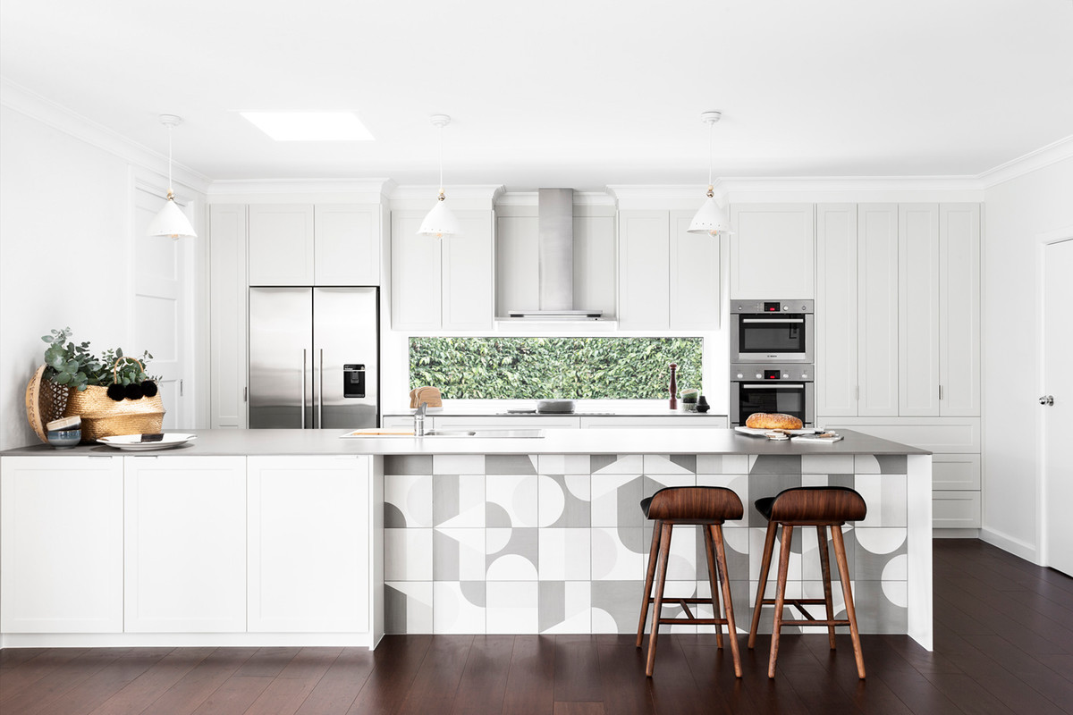 Inspiration for a mid-sized scandinavian galley dark wood floor and brown floor open concept kitchen remodel in Melbourne with a drop-in sink, shaker cabinets, white cabinets, window backsplash, stainless steel appliances, a peninsula, concrete countertops and white countertops