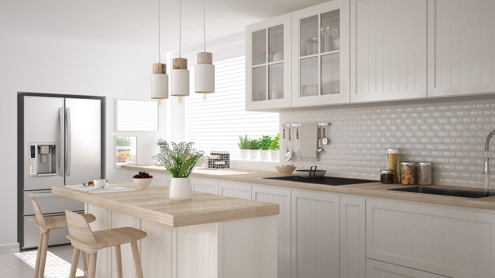 Example of a mid-sized cottage chic single-wall light wood floor and beige floor enclosed kitchen design in Miami with a drop-in sink, louvered cabinets, white cabinets, wood countertops, white backsplash, porcelain backsplash, stainless steel appliances and an island