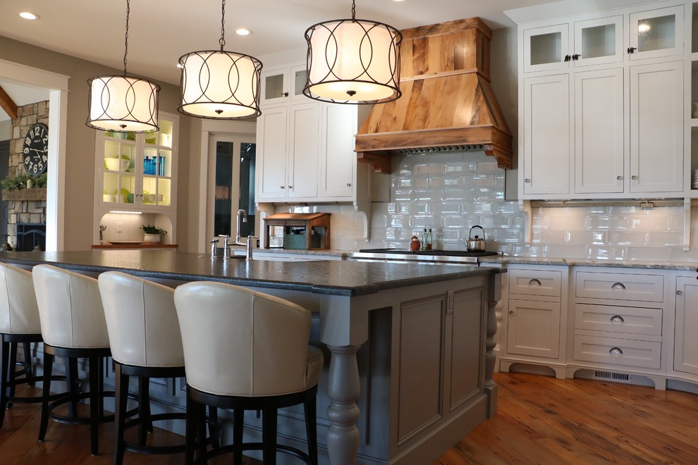 Open concept kitchen - large country medium tone wood floor open concept kitchen idea in Other with a farmhouse sink, shaker cabinets, white cabinets, granite countertops, gray backsplash, porcelain backsplash, stainless steel appliances, an island and gray countertops