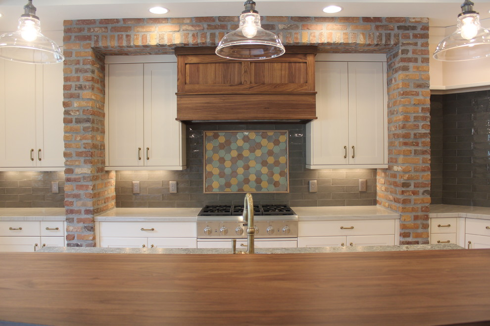 Example of a large transitional u-shaped open concept kitchen design in Salt Lake City with a farmhouse sink, shaker cabinets, white cabinets, subway tile backsplash, stainless steel appliances and an island