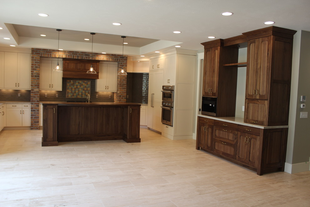 Inspiration for a large transitional u-shaped open concept kitchen remodel in Salt Lake City with a farmhouse sink, shaker cabinets, white cabinets, subway tile backsplash, stainless steel appliances and an island