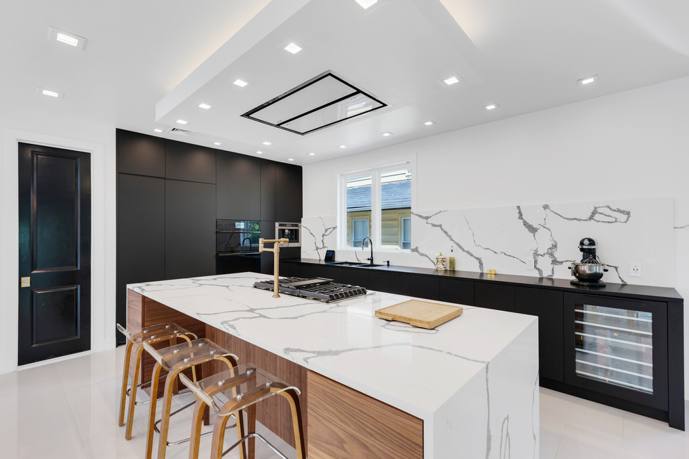 Example of a trendy l-shaped marble floor and white floor kitchen design in New York with flat-panel cabinets, black cabinets, quartzite countertops, a double-bowl sink, white backsplash, black appliances, an island and white countertops