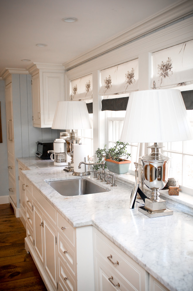 Eat-in kitchen - mid-sized cottage single-wall dark wood floor eat-in kitchen idea in Manchester with a single-bowl sink, marble countertops, white cabinets, stainless steel appliances and raised-panel cabinets