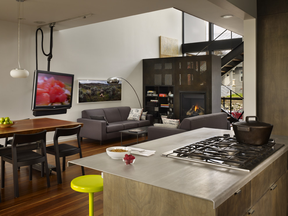 Inspiration for a small modern galley medium tone wood floor open concept kitchen remodel in Seattle with an undermount sink, flat-panel cabinets, medium tone wood cabinets, stainless steel countertops, stainless steel appliances and an island