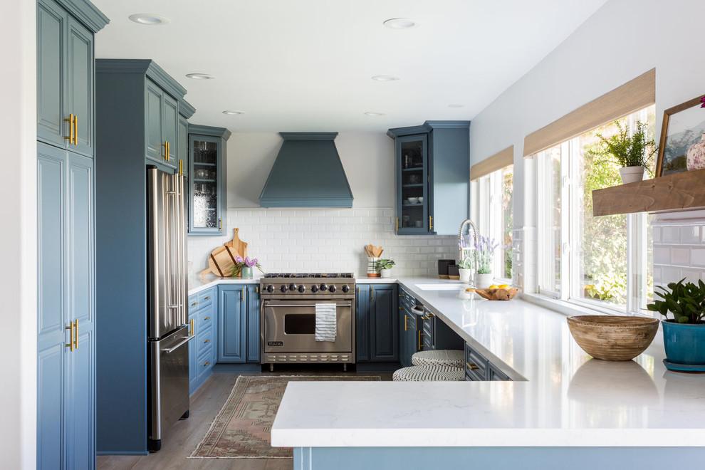 Kitchen - coastal u-shaped kitchen idea in Los Angeles with a single-bowl sink, raised-panel cabinets, blue cabinets, white backsplash, subway tile backsplash, stainless steel appliances, a peninsula and white countertops