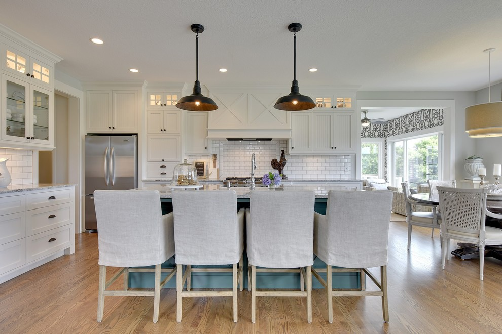 Cottage l-shaped medium tone wood floor eat-in kitchen photo in Minneapolis with white cabinets, granite countertops, white backsplash, ceramic backsplash, stainless steel appliances, an island and shaker cabinets