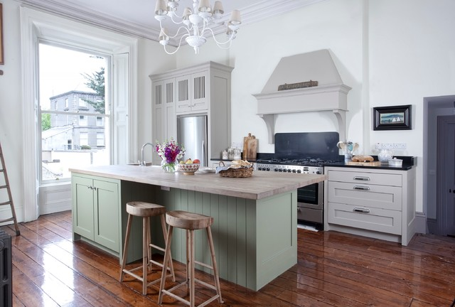 Example of a classic dark wood floor kitchen design in Dublin with shaker cabinets, green cabinets and an island