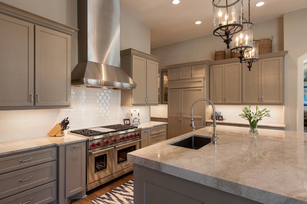 Elegant dark wood floor kitchen photo in Houston with an undermount sink, recessed-panel cabinets, beige cabinets, white backsplash, subway tile backsplash, stainless steel appliances, an island and beige countertops