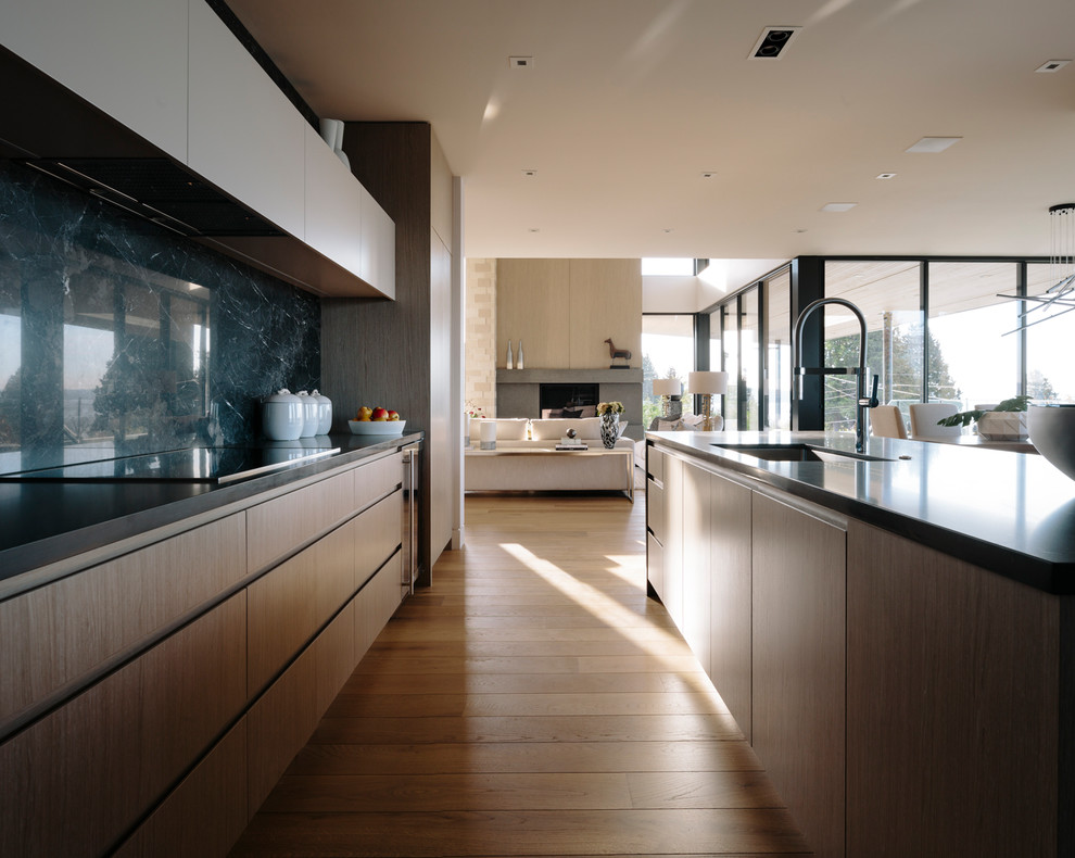 Example of a large trendy galley medium tone wood floor eat-in kitchen design in Vancouver with an undermount sink, flat-panel cabinets, medium tone wood cabinets, quartz countertops, gray backsplash, porcelain backsplash, stainless steel appliances, an island and gray countertops