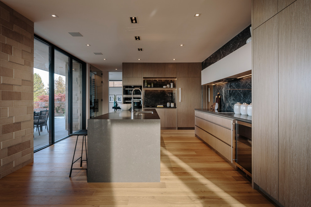 Inspiration for a large contemporary galley medium tone wood floor eat-in kitchen remodel in Vancouver with an undermount sink, flat-panel cabinets, medium tone wood cabinets, quartz countertops, gray backsplash, porcelain backsplash, stainless steel appliances, an island and gray countertops