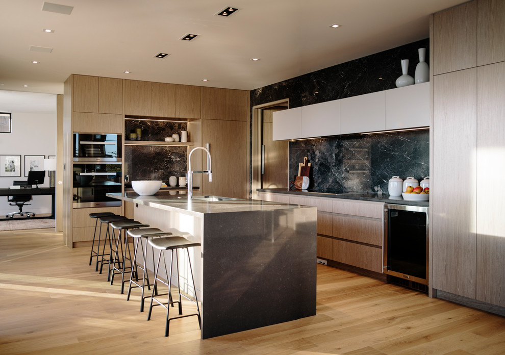 Eat-in kitchen - large contemporary galley medium tone wood floor eat-in kitchen idea in Vancouver with an undermount sink, flat-panel cabinets, medium tone wood cabinets, quartz countertops, gray backsplash, porcelain backsplash, stainless steel appliances, an island and gray countertops