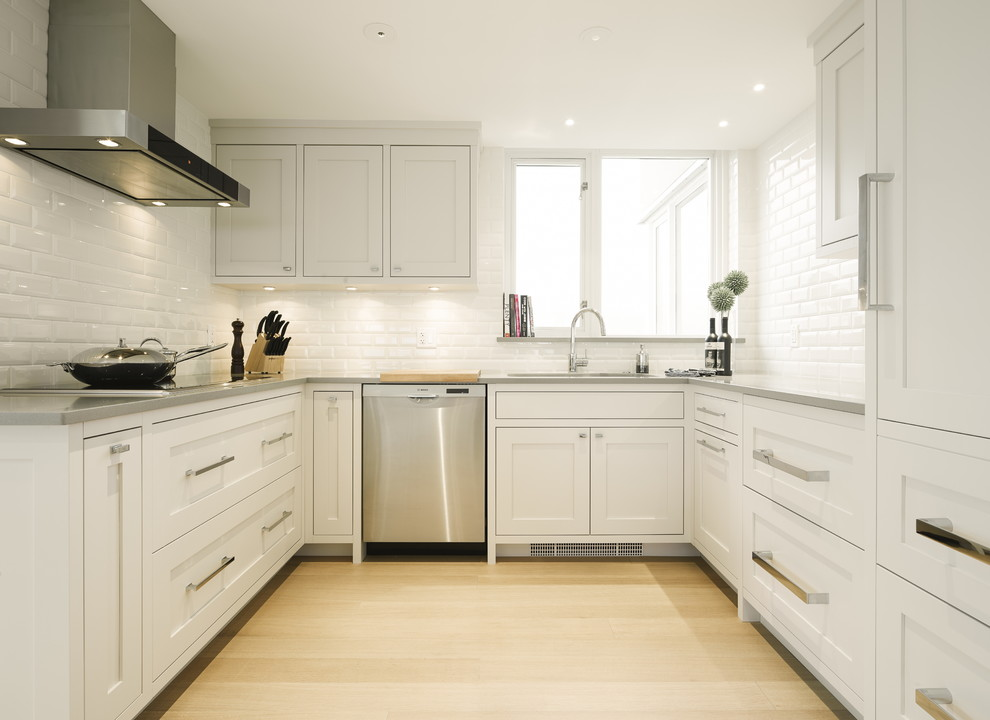 Example of a mid-sized transitional u-shaped light wood floor eat-in kitchen design in Vancouver with an undermount sink, shaker cabinets, gray cabinets, quartz countertops, white backsplash, ceramic backsplash, stainless steel appliances and an island