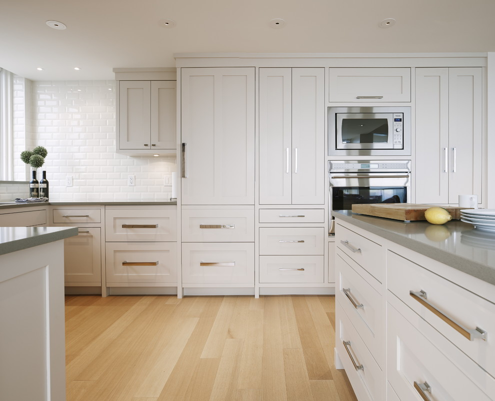 Inspiration for a mid-sized transitional u-shaped light wood floor eat-in kitchen remodel in Vancouver with an undermount sink, shaker cabinets, gray cabinets, quartz countertops, white backsplash, ceramic backsplash, stainless steel appliances and an island