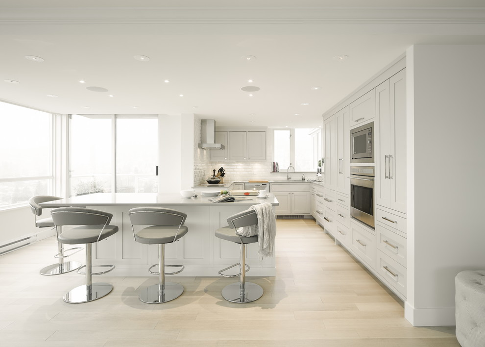 Inspiration for a mid-sized transitional u-shaped light wood floor kitchen remodel in Vancouver with an undermount sink, shaker cabinets, gray cabinets, quartz countertops, white backsplash, ceramic backsplash, stainless steel appliances and an island