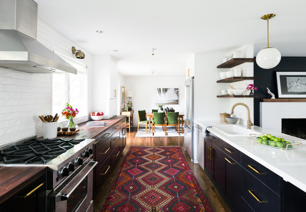 Eat-in kitchen - transitional galley medium tone wood floor eat-in kitchen idea in Seattle with a drop-in sink, flat-panel cabinets, black cabinets, white backsplash, stainless steel appliances and a peninsula