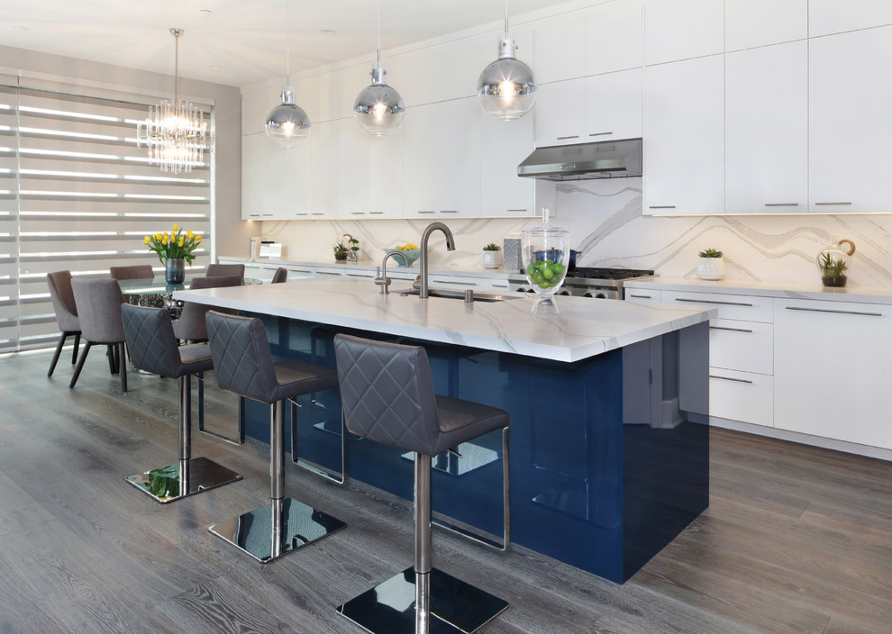 Example of a mid-sized minimalist l-shaped medium tone wood floor and gray floor eat-in kitchen design with an undermount sink, flat-panel cabinets, white cabinets, quartz countertops, white backsplash, stone slab backsplash, stainless steel appliances, an island and white countertops