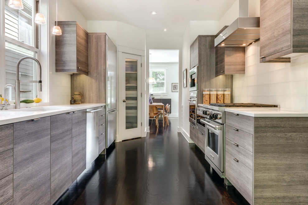 Inspiration for a large contemporary galley dark wood floor eat-in kitchen remodel in Seattle with an undermount sink, flat-panel cabinets, medium tone wood cabinets, quartz countertops, white backsplash, glass tile backsplash, stainless steel appliances and no island