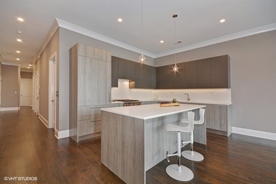 Open concept kitchen - large contemporary l-shaped medium tone wood floor open concept kitchen idea in Chicago with an undermount sink, flat-panel cabinets, beige cabinets, quartz countertops, beige backsplash, paneled appliances and an island