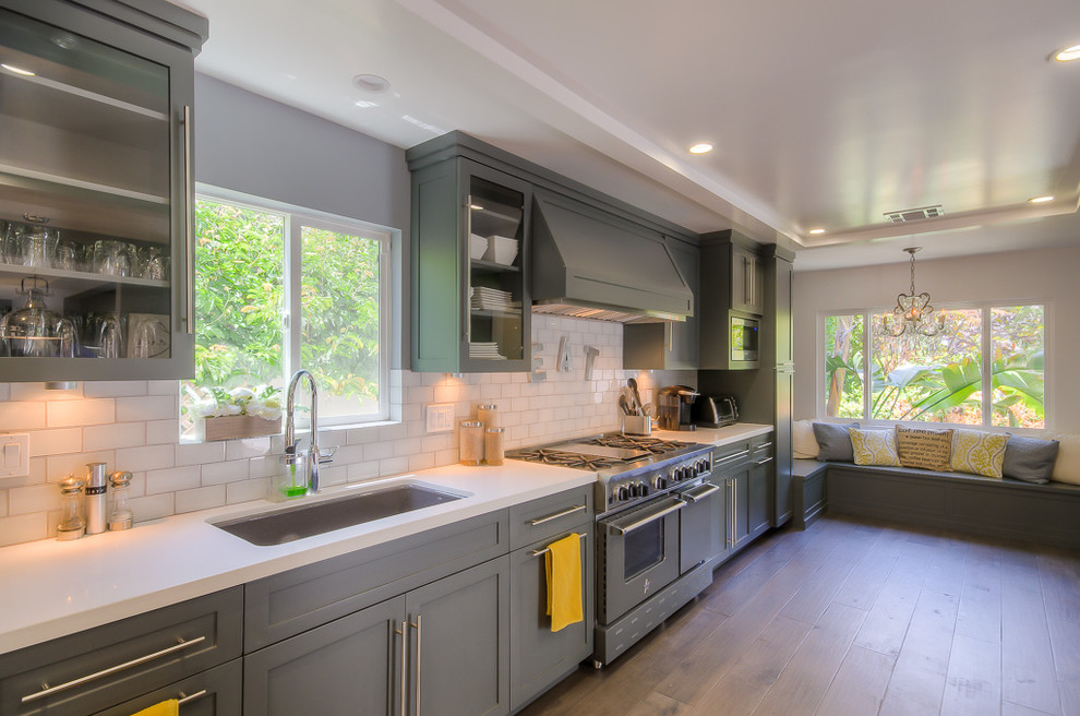 Example of a large transitional single-wall medium tone wood floor kitchen design in Los Angeles with an undermount sink, shaker cabinets, gray cabinets, white backsplash, subway tile backsplash and stainless steel appliances