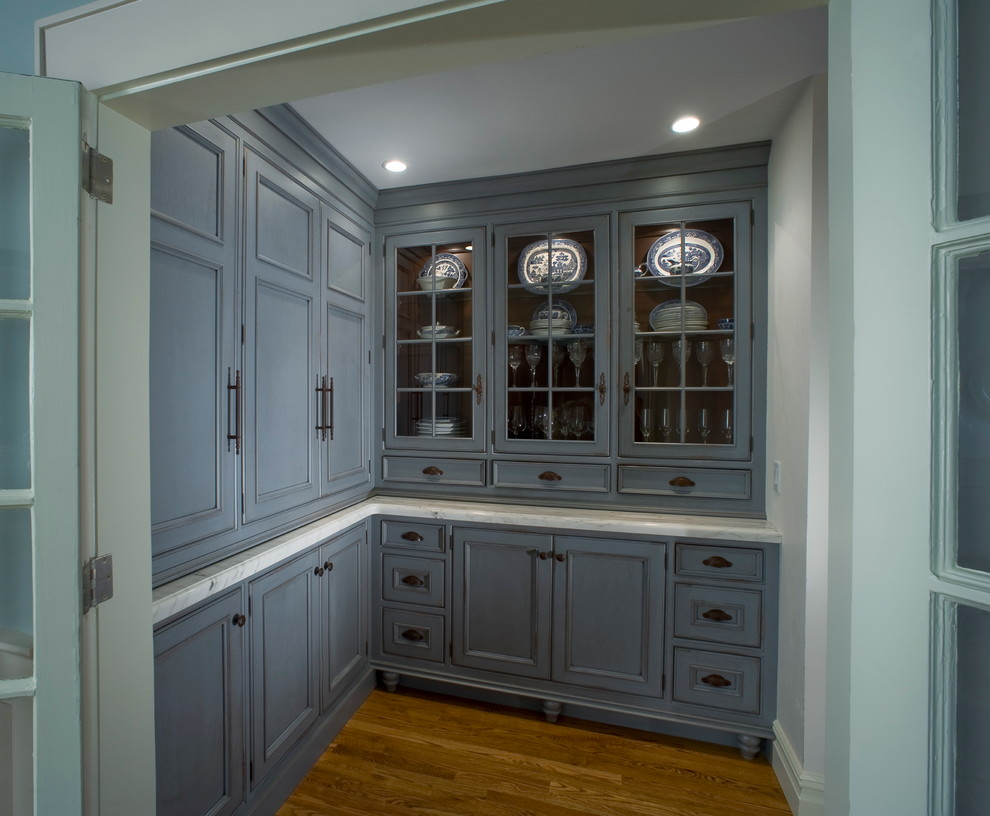 Kitchen pantry - mid-sized traditional l-shaped medium tone wood floor kitchen pantry idea in New York with beaded inset cabinets, blue cabinets, marble countertops and no island