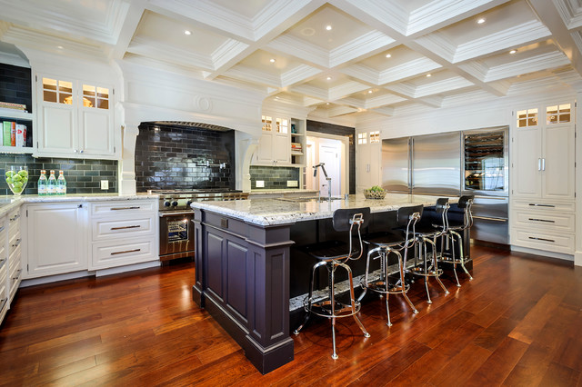 This is an example of a large traditional l-shaped kitchen in San Francisco with raised-panel cabinets, stainless steel appliances, metro tiled splashback, white cabinets, granite worktops, grey splashback, medium hardwood flooring, an island and brown floors.