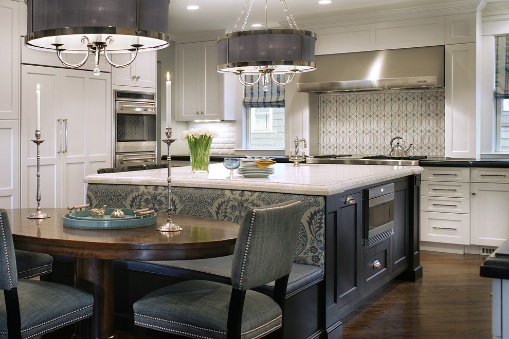 Transitional u-shaped eat-in kitchen photo in New York with a farmhouse sink, recessed-panel cabinets, granite countertops, gray backsplash, glass tile backsplash, stainless steel appliances and white cabinets