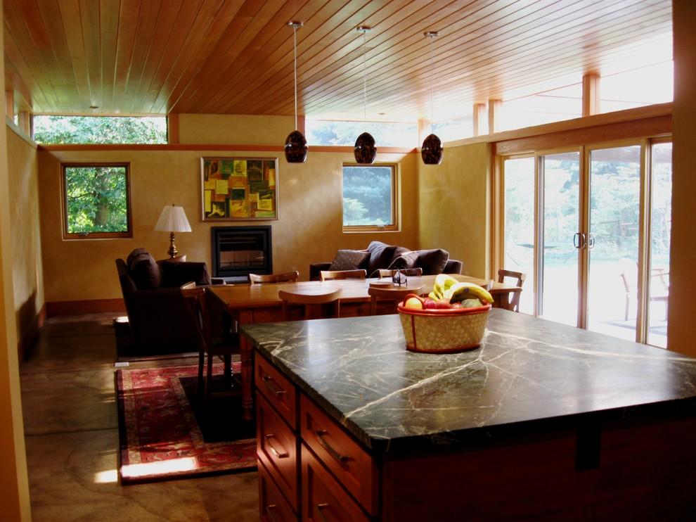 Modelo de cocina actual con armarios estilo shaker, puertas de armario de madera oscura, encimera de mármol y suelo de cemento