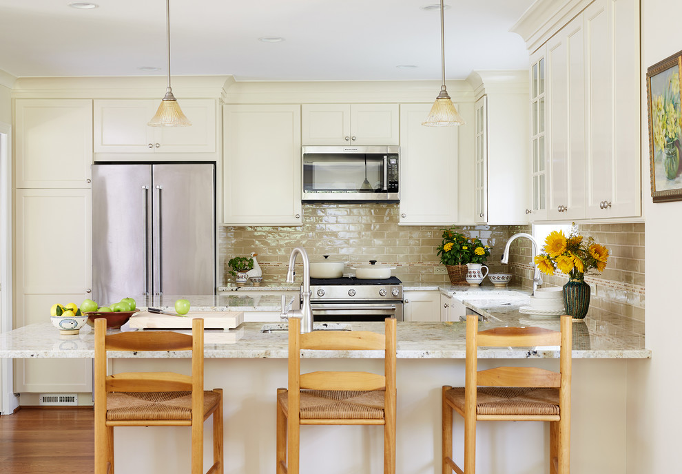 Inspiration for a timeless u-shaped medium tone wood floor kitchen remodel in DC Metro with a farmhouse sink, shaker cabinets, beige cabinets, beige backsplash, subway tile backsplash, stainless steel appliances and a peninsula
