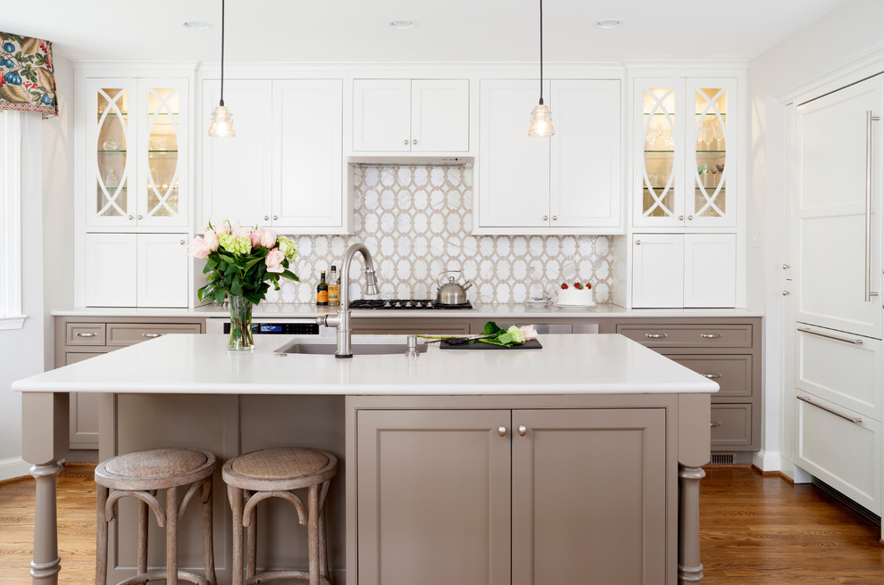 Example of a mid-sized transitional l-shaped medium tone wood floor eat-in kitchen design in DC Metro with white cabinets, white backsplash, stainless steel appliances, an island, an undermount sink and recessed-panel cabinets