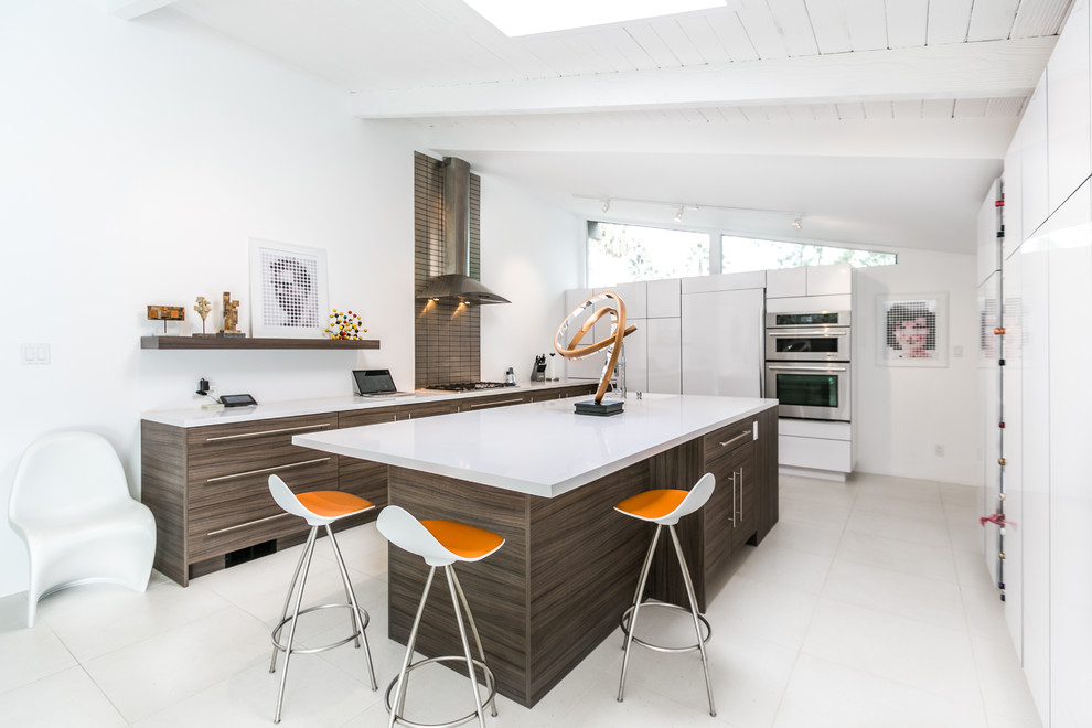 Example of a 1960s u-shaped kitchen design in Seattle with flat-panel cabinets, stainless steel appliances and an island
