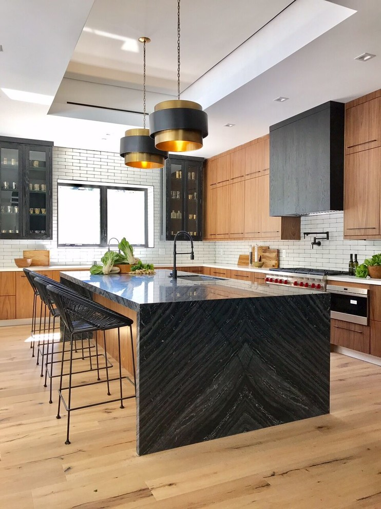 Inspiration for a contemporary l-shaped open concept kitchen remodel in Los Angeles with flat-panel cabinets, stainless steel cabinets, white backsplash, subway tile backsplash, stainless steel appliances and an island