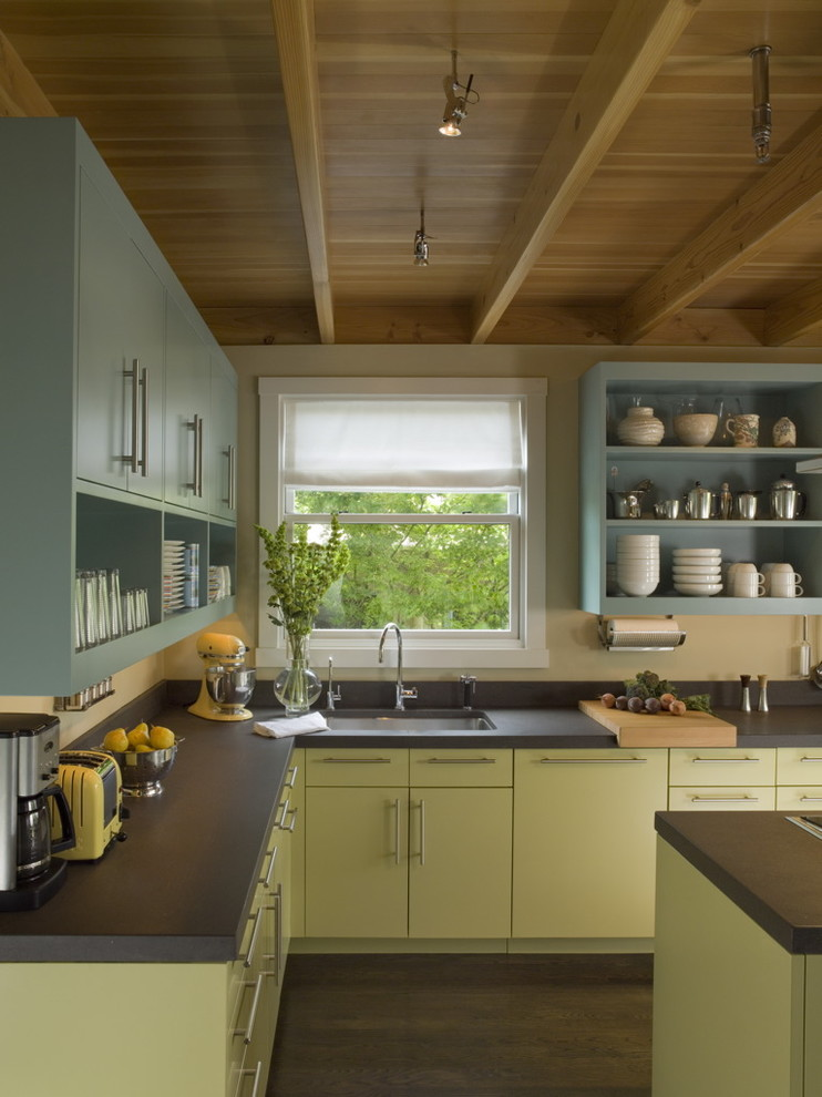 Open concept kitchen - mid-sized contemporary l-shaped dark wood floor open concept kitchen idea in San Francisco with open cabinets, paneled appliances, an island, an undermount sink, green cabinets and black backsplash