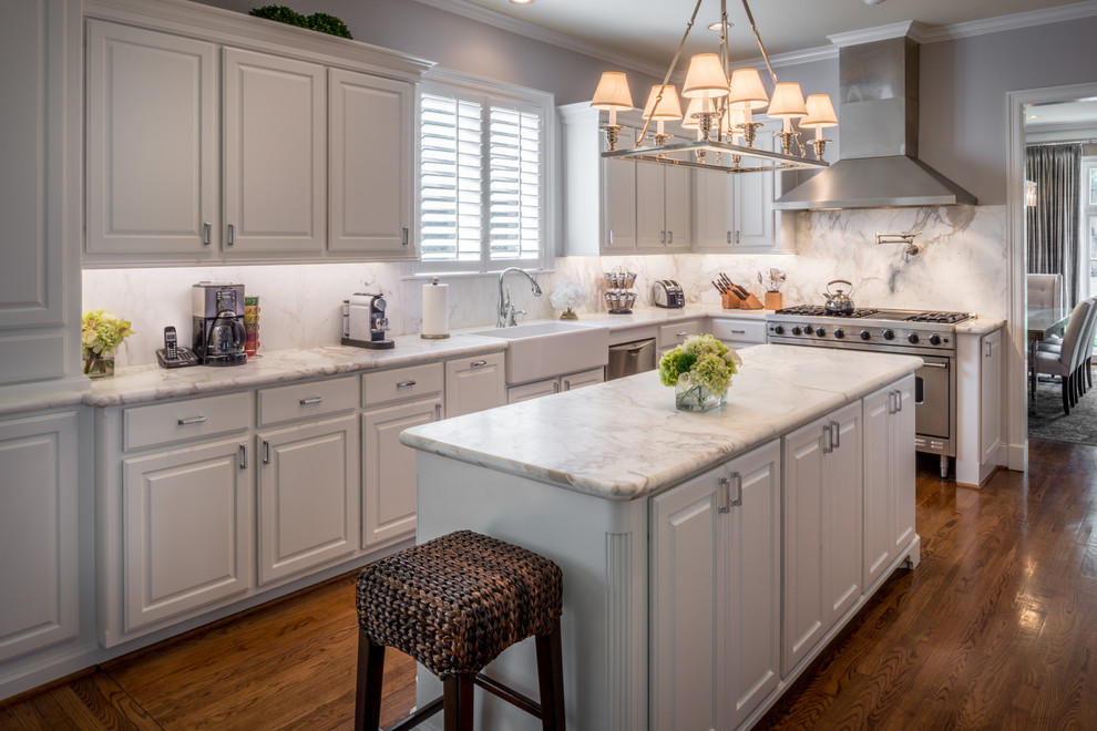 Inspiration for a large timeless l-shaped medium tone wood floor eat-in kitchen remodel in Houston with a farmhouse sink, white cabinets, marble countertops, white backsplash, stone slab backsplash, stainless steel appliances and an island