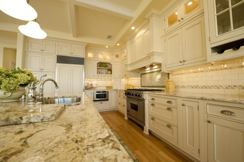 Enclosed kitchen - mid-sized traditional galley medium tone wood floor enclosed kitchen idea in New York with a double-bowl sink, recessed-panel cabinets, white cabinets, granite countertops, beige backsplash, ceramic backsplash, paneled appliances and an island