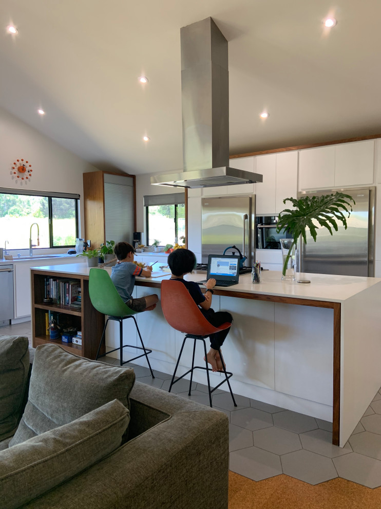 Mid-sized 1960s l-shaped porcelain tile, gray floor and vaulted ceiling open concept kitchen photo in San Diego with an undermount sink, flat-panel cabinets, white cabinets, quartz countertops, white backsplash, quartz backsplash, stainless steel appliances, an island and white countertops