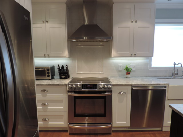 Eat-in kitchen - mid-sized transitional l-shaped light wood floor eat-in kitchen idea in Montreal with a farmhouse sink, shaker cabinets, white cabinets, granite countertops, white backsplash, ceramic backsplash, stainless steel appliances and an island