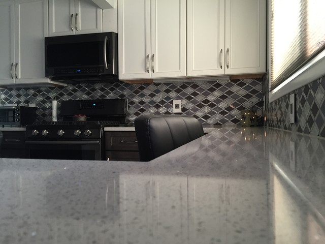 black and white kitchen with stainless steel backsplash