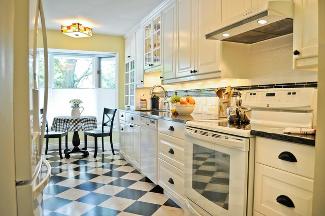 Eat-in kitchen - mid-sized traditional galley linoleum floor eat-in kitchen idea in Ottawa with louvered cabinets, white cabinets, quartzite countertops, white backsplash, subway tile backsplash and white appliances