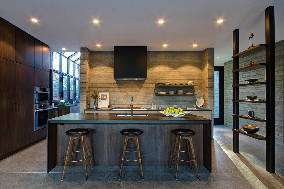 Large cottage l-shaped concrete floor open concept kitchen photo in San Francisco with an undermount sink, flat-panel cabinets, dark wood cabinets, paneled appliances and an island