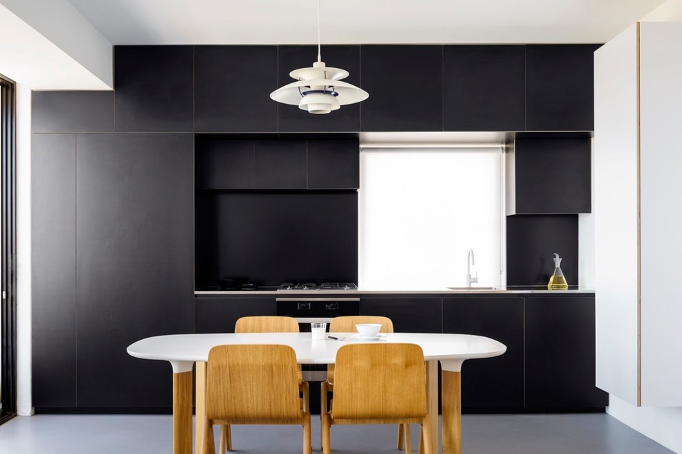 Small contemporary single-wall separate kitchen in Sydney with an undermount sink, black splashback, stainless steel appliances, concrete floors, grey floor, black cabinets, stainless steel benchtops and no island.